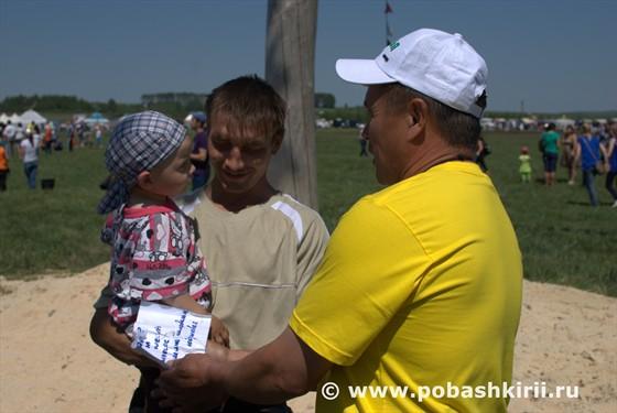 Женя получает приз за подъем на столб во время Сабантуя 2012 года